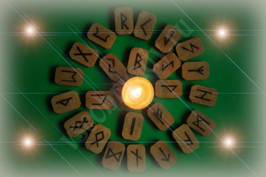 руны, камешки и свеча вокруг